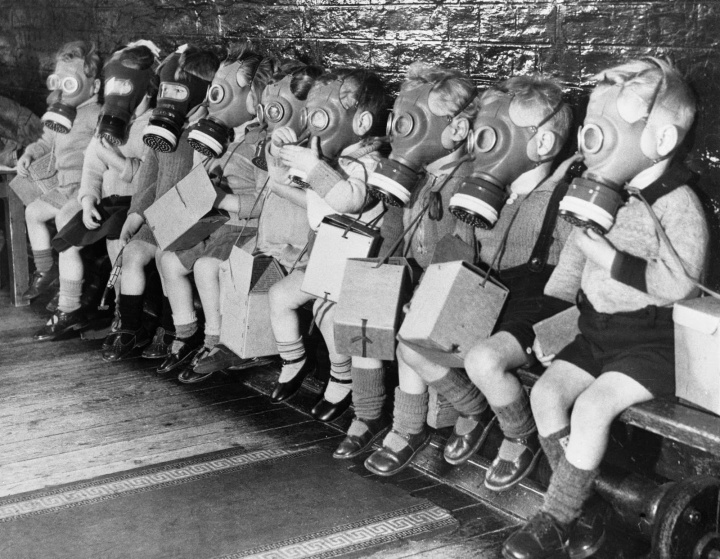 Toddlers on bench in gas masks during WWII